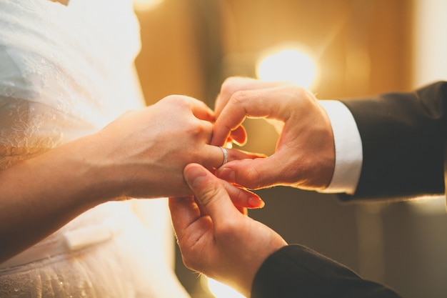 The groom places the ring on the bride's hand. the hands of the newlyweds.