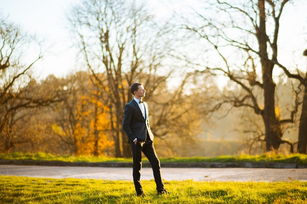Groom posing in the park at sunset