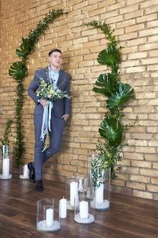 結婚式の準備をしている新郎。未来の夫が未来の妻を待っています。結婚式の前に、結婚式のスーツを着た男性が写真家のポーズをとります。幸せな男の肖像