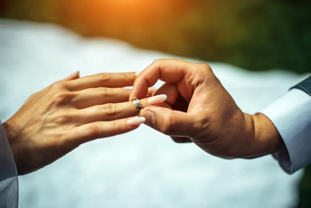 新郎は花嫁の指に金の結婚指輪を置いて、クローズアップ。結婚式、指輪の交換。