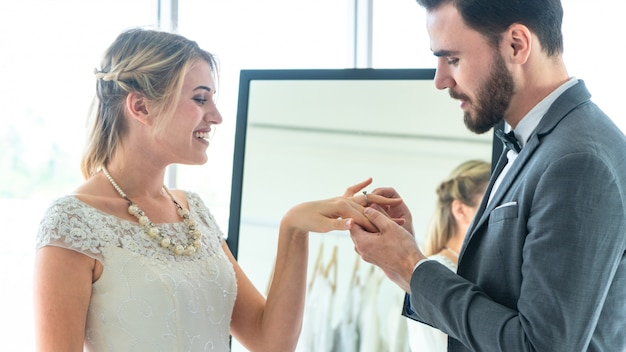 Groom put a ring on finger of his lovely bride in wedding fashion dress up interior studio with wear suit and bride dress.