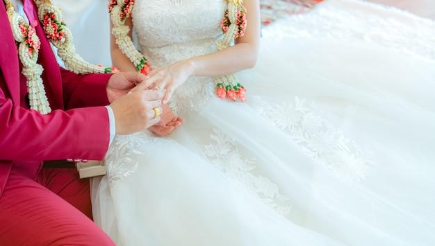 新郎は結婚式の日に提案のために花嫁の指に結婚式のダイヤモンドリングを置きます。白いウェディングドレスと赤いスーツと結婚式の花輪の新郎新婦。
