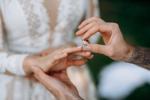 Жених надевает обручальное кольцо невесты