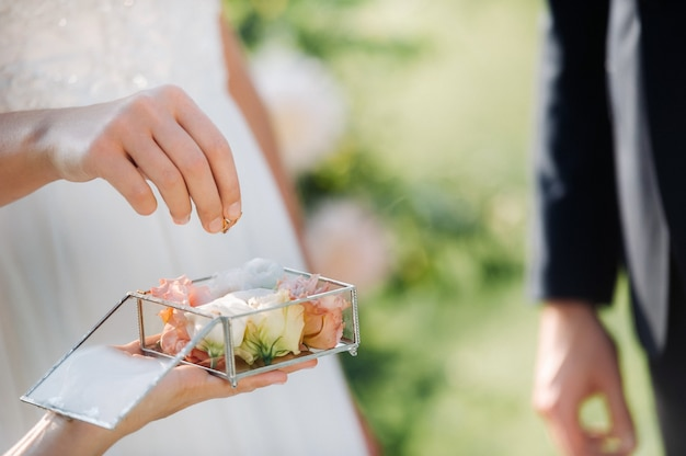 The groom puts an engagement ring on the bride's finger on their wedding day. Premium Photo