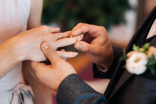 The groom puts an engagement ring on the bride's finger on their wedding day.