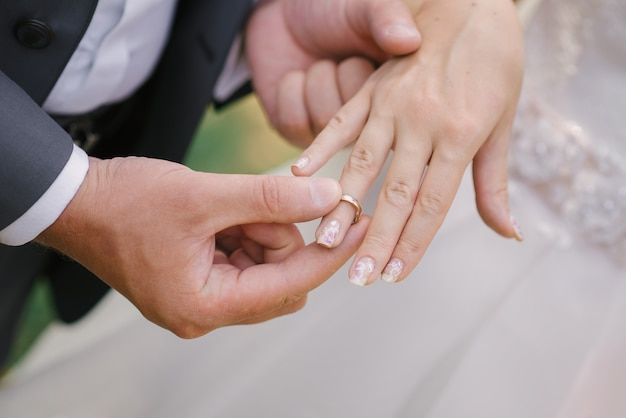 The groom puts on a finger ring wedding bride.