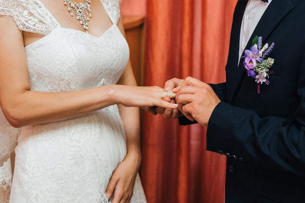 Groom puts a gold wedding ring on the bride finger