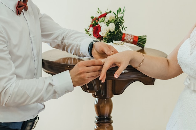 Groom puts a gold wedding ring on the bride's finger
