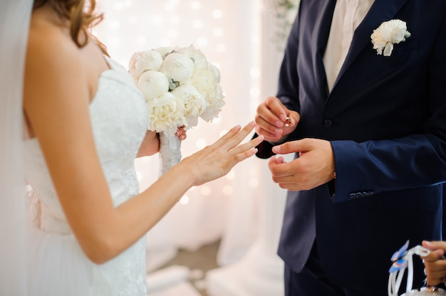 Groom puts on a gold wedding ring on the finger of a beautiful bride