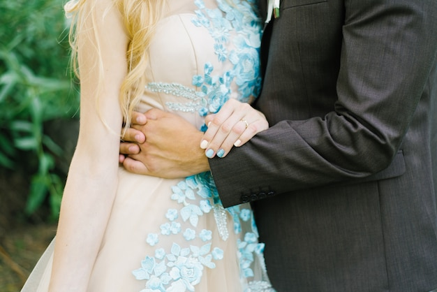 Groom puts his arm around the waist of the bride
