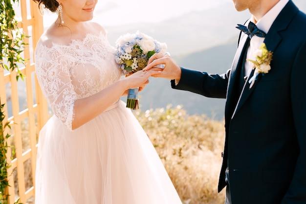 신랑은 그녀가 웃고있는 신부 손가락에 결혼 반지를 넣습니다.