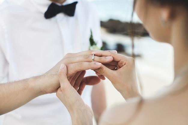 Жених кладет кольцо на палец невесты во время свадебной церемонии