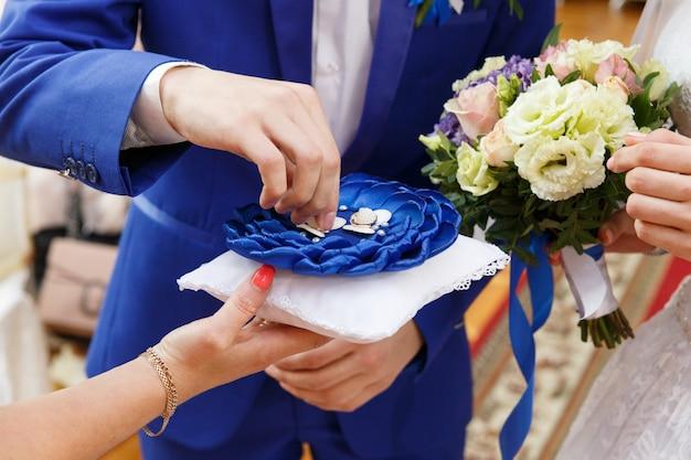 Жених надевает кольцо на палец невесты во время свадебной церемонии