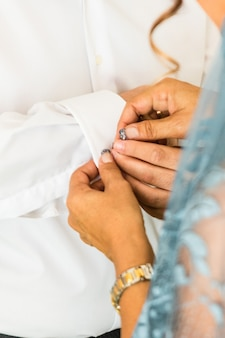 A groom putting on cuff-links as he gets dressed in his wedding day. groom's suit