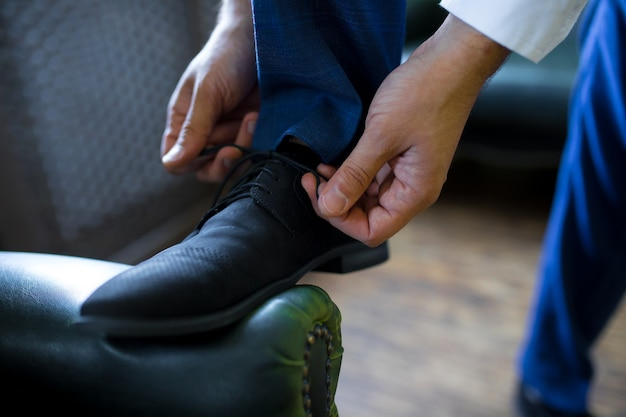 Жених надевает свадебные туфли.