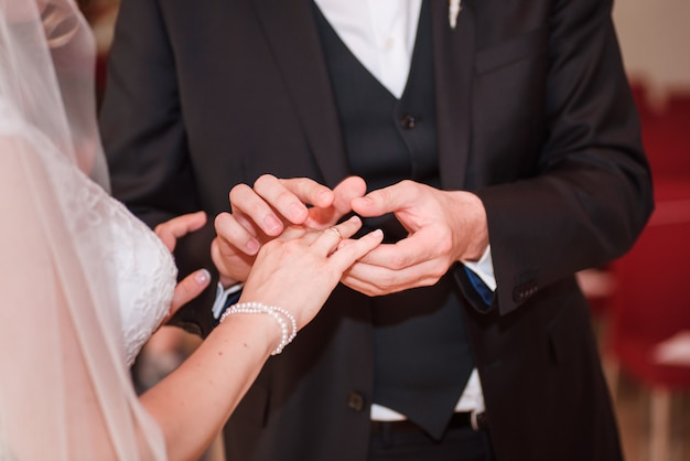 Groom putting a ring on bride's finger.