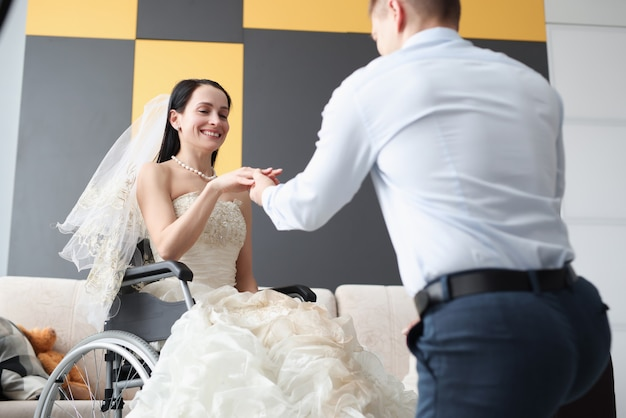 Groom putting ring on finger of bride in wheelchair. full life of disabled people concept