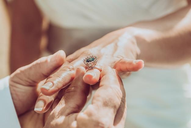 新郎が花嫁の手に指輪を置く。