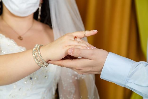 マスクをした花嫁のユダヤ人の結婚式の手のクローズアップで人差し指の人差し指に指輪を置く新郎。横の写真。