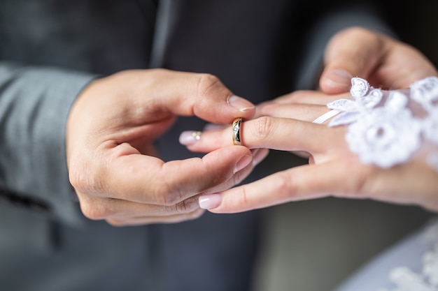 Groom putting the wedding ring on bride finger close up.