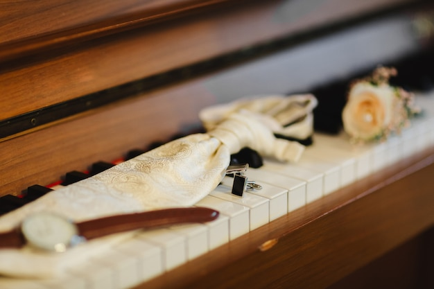 Groom's accessories. stylish watch, tie, boutonniere and cufflinks on the keys for piano.