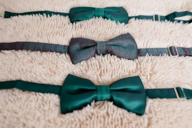 白いじゅうたんの上に新郎と最高の男性の緑の蝶ネクタイ