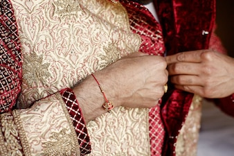 Groom's arms with red bracelet button up golden wedding suit