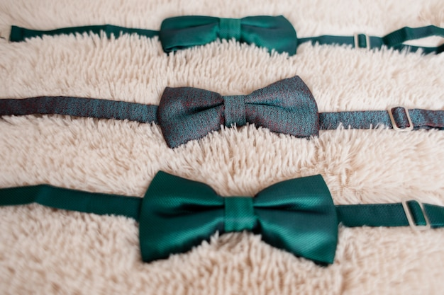 Groom's and best men's green bow ties on the white carpet