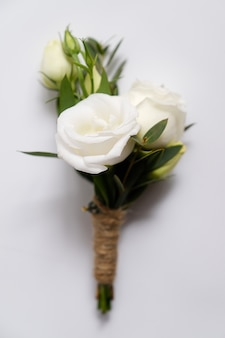 Groom's boutonniere of white roses and green leaves. wedding paraphernalia and accessory.