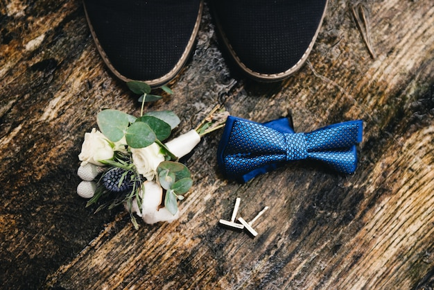 Groom's bow tie and boutonniere on a wet wooden