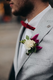 The groom's burgundy boutonniere . the groom in a jacket.