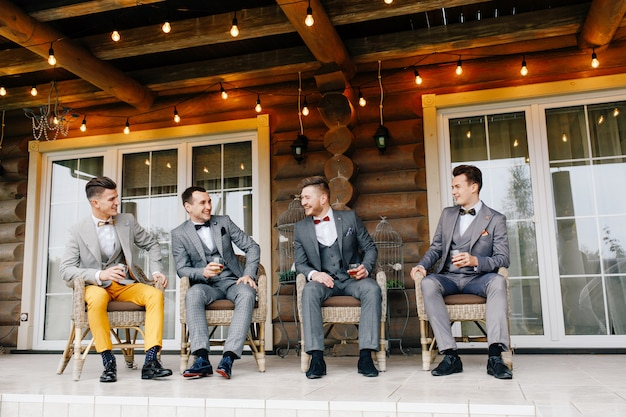 The groom's friends sit on the terrace of the house and drink whiskey