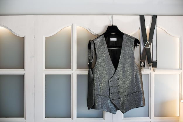 Groom's new waistcoat, tie and suspenders hanging on a hanger on a window.