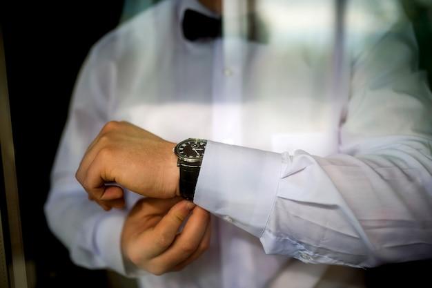신랑의 결혼식 준비. 신랑은 재킷에 단추를 끼 웁니다. 결혼식 흑백 사진 개념입니다. 확대.