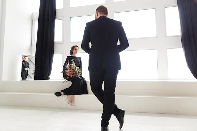 Groom's reflection in mirror. bride sitting on stairs in white studio near window