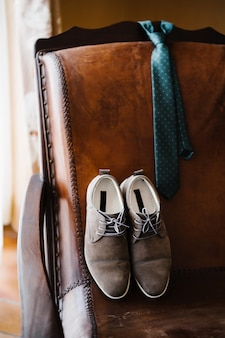 Groom's shoes and polka dot tie on a leather chair in the room.