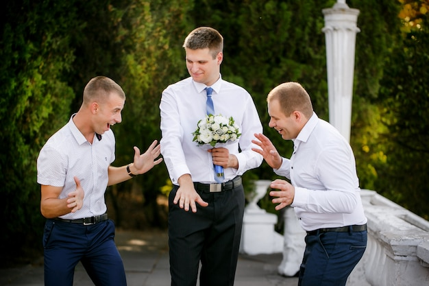 Groom shows a wedding ring to friends