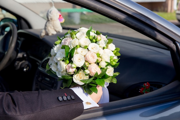The groom sitting in car holding bouquet for bride