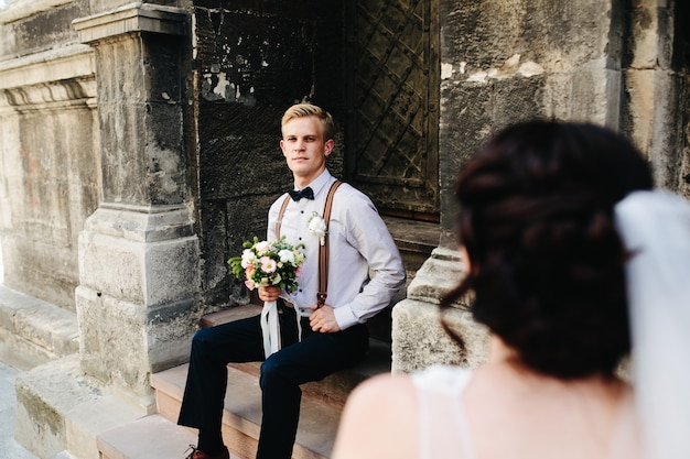 石段に座っている新郎とカメラのポーズ