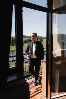 Groom stand in window by balcony at hotel. handsome groom waiting for bride