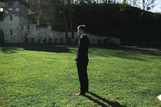 Sposo in piedi sull'erba e in attesa della sposa