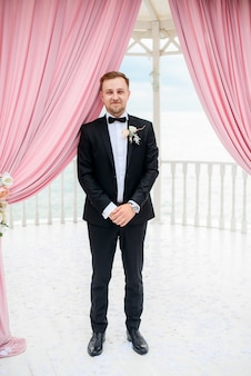 Groom stands alone under the tent for wedding ceremony by the sea