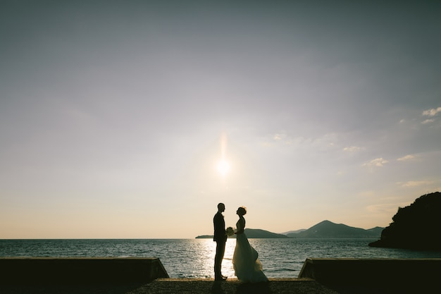 Groom stands in front of bride in a white dress with a bouquet of flowers on the embankment by the