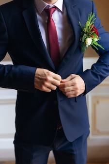 The groom in a stylish blue suit and red tie buttoned his jacket beautiful boutonniere