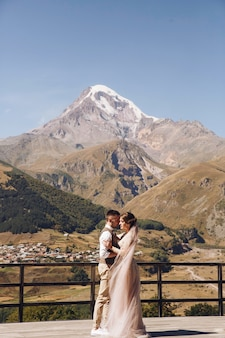 Groom in suit and bride in charming pink dress on the terasse with great mountain view
