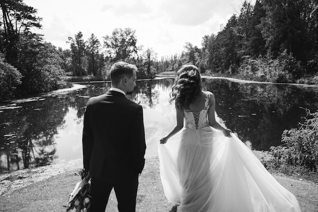 The groom in a suit and the bride in a white dress standing on the shore of a mountain lake