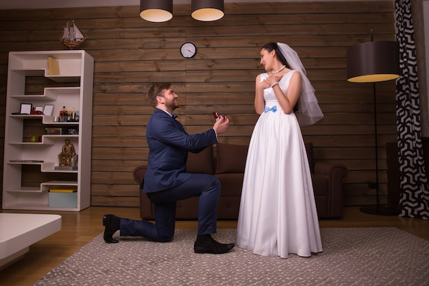 Groom in suit holding wedding rings, standing on his knees and making a proposal of marriage to happy bride in white dress and veil
