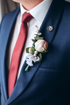 The groom in a suit and red tie