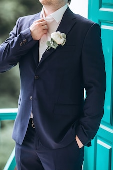 The groom in a suit straightens his tie