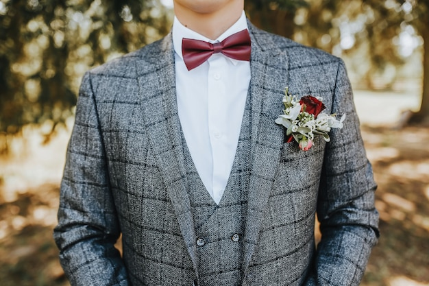 Groom in a suit with a wedding flower boutonniere and a red bow tie in nature